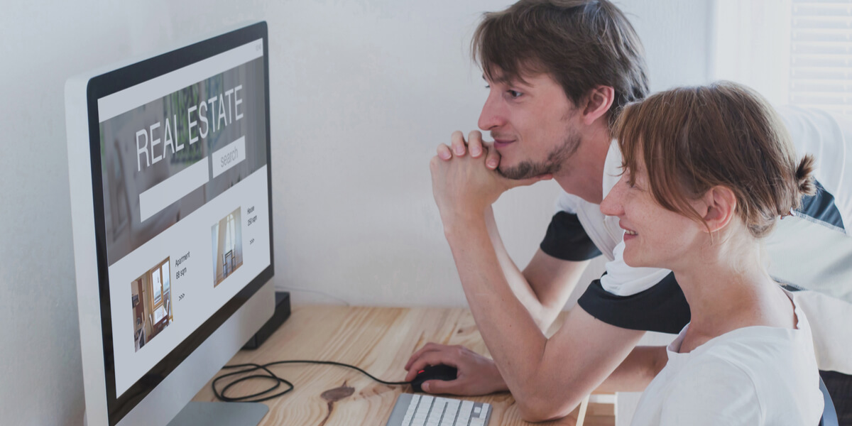 Young couple looking at real estate website.